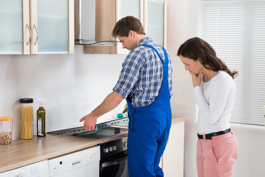 appliance tech repairing stove top